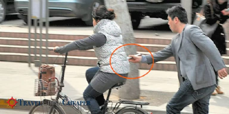 A thief in China swipes an phone from a passing lady