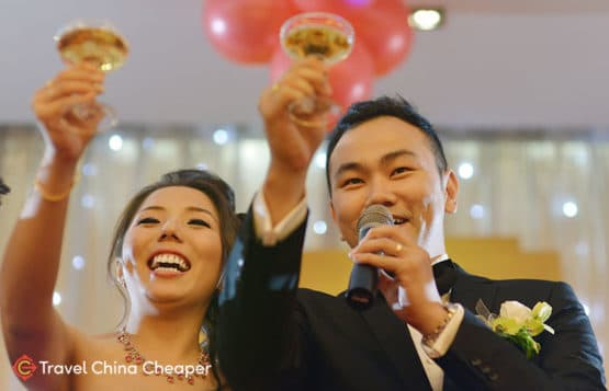A Chinese bride and groom toasting during their wedding using Chinese alcohol