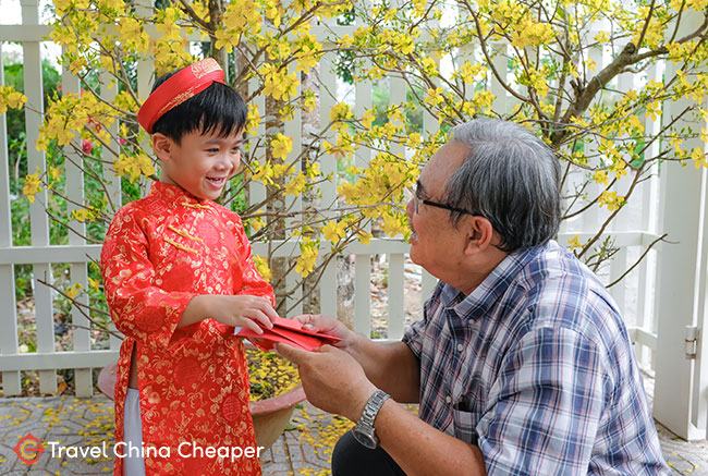 A grandparent gives a child a hongbao with money in China