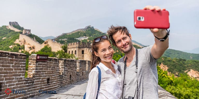 Travelers on the Great Wall of China taking a photo with their mobile phone