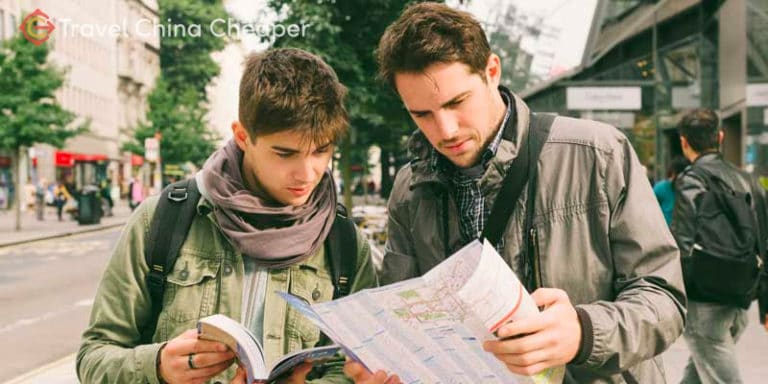 Two travelers using a physical travel map in China.